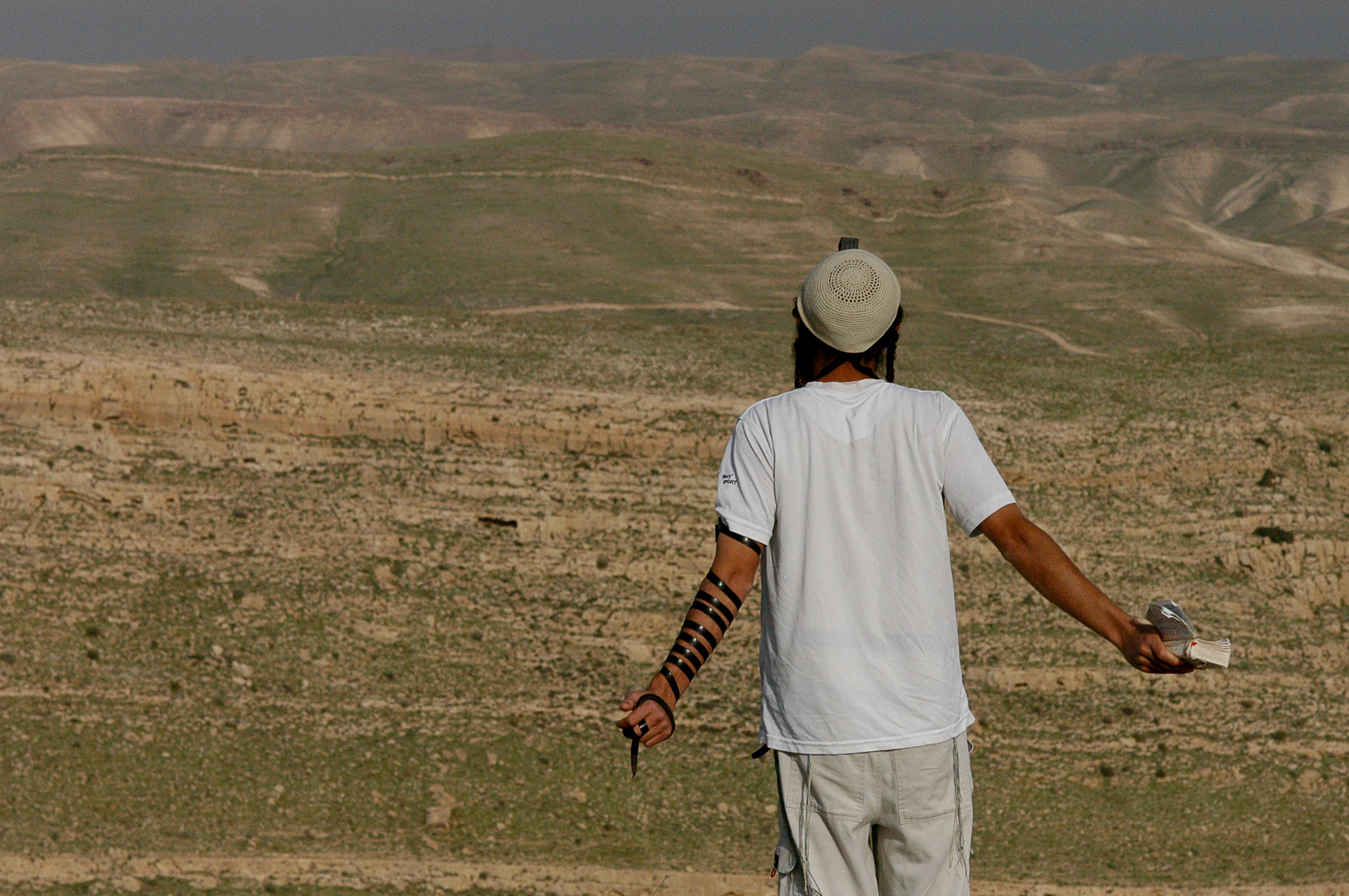 Facing east towards the Judean desert, a Jewish settler conducts a mid-day prayer, at the unauthorized Jewish outpost of Tekoa D, West Bank.  March 1, 2004 Photo by Ahikam Seri/backyard